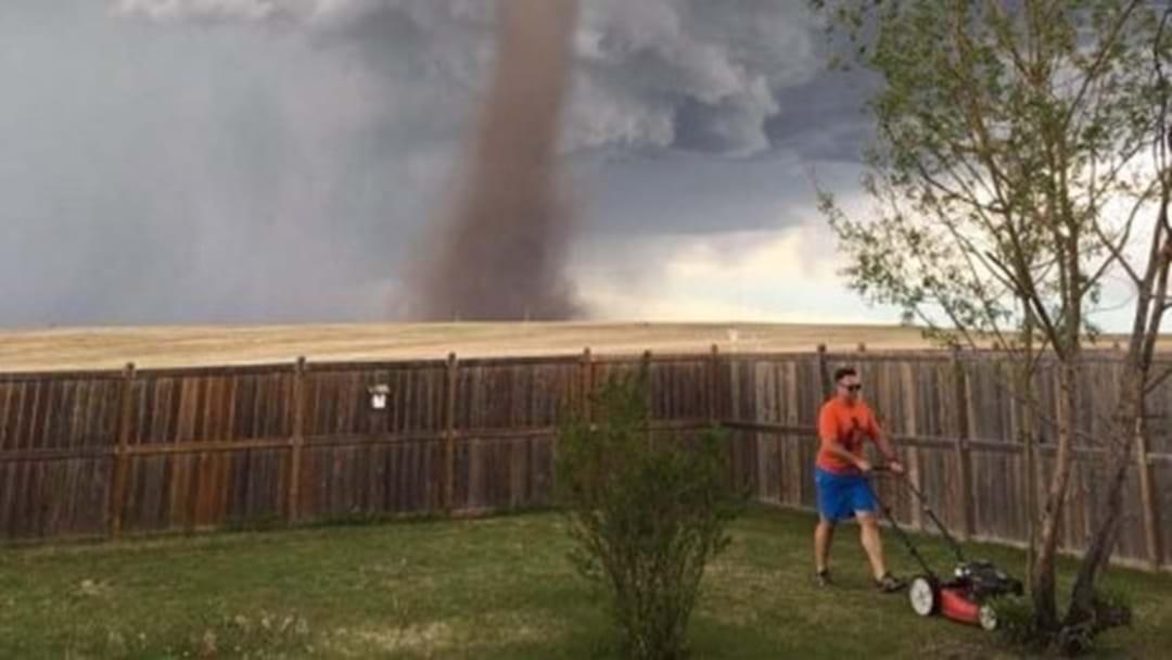 Man Cuts Grass While Tornado Tears Past