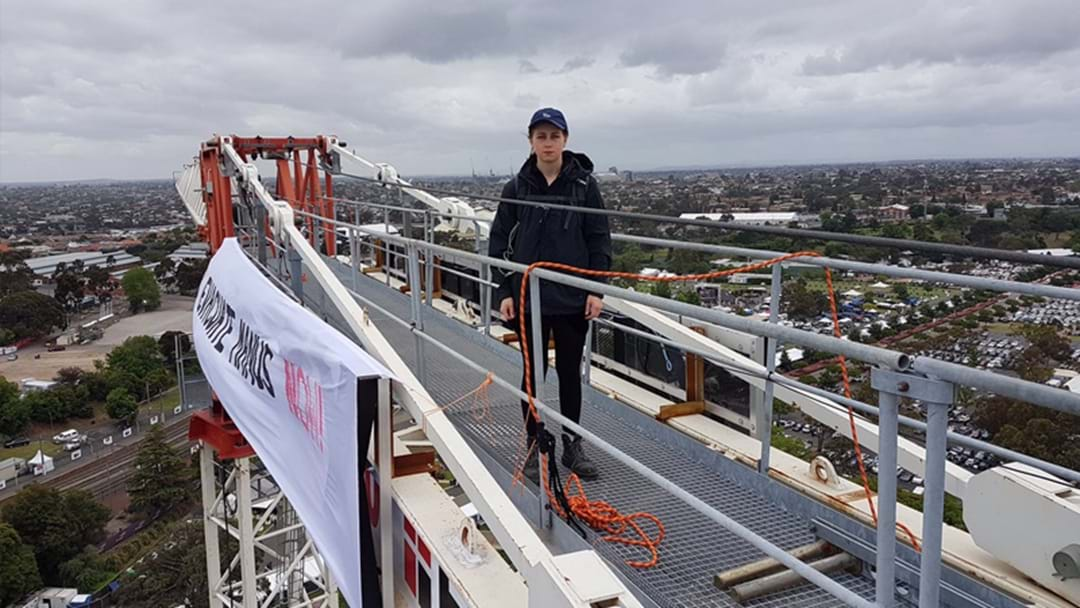 Manus Island Protesters Scale A Crane And Unfurl A Banner Over Flemington
