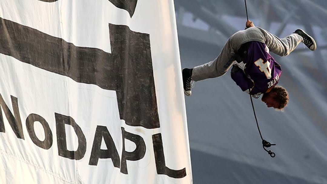 Protestors Hung From The Roof To Unfurl A Huge Banner At An NFL Game This Morning